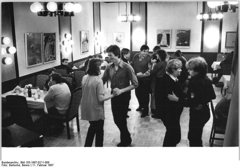 """Dorfdisco in der DDR 1987 [ADN-ZB Bartocha 11.2.87 Bez. Neubrandenburg: Nienhagen - Patendorf der FDJ- Disco in der Dorfgaststätte ist eine der neuesten Errungenschaften für die jungen Leute in Nienhagen. Die Gaststätte """"Am Ziegenmarkt"""" ist Eigentum der LPG. Sie gehört im weiten Umkreis des Dorfes zu denen, die keine Konkurrenz zu scheuen brauchen. Die Einrichtung wird von einem Ehepaar betrieben, das aus dem Bezirk Dresden kam und eines der neuen Eigenheime bezog. - siehe auch 1987-0211-9 und 10N -; Foto Benno Bartocha, Bundesarchiv, Bild 183-1987-0211-008 / CC-BY-SA 3.0]"""